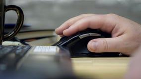 A mão da opinião lateral do close up guarda o rato e funciona com portátil video estoque