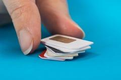 Mão da pessoa que coloca a pilha de cartão do sim Imagens de Stock Royalty Free