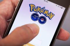 A mão da pessoa que começa Pokemon vai aplicação na maçã iPhone5s Fotos de Stock Royalty Free