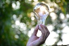 Mão da pessoa que guarda a ampola para a ideia ou o sucesso ou energia solar Imagens de Stock