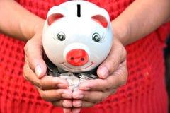 A mão da pessoa que guarda moedas e sentimento do mealheiro salvar o dinheiro e o sucesso, finança Foto de Stock