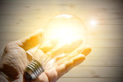 A mão da pessoa que guarda um bulbo e ilumina muitos brilhantes para fora do bulbo Imagens de Stock