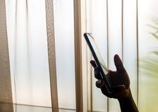 A mão da pessoa que guarda um telefone celular dentro, ao lado de uma janela imagens de stock