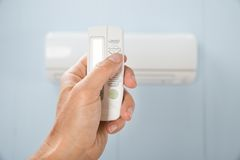 Mão da pessoa que mantém o condicionador de ar remoto Fotografia de Stock