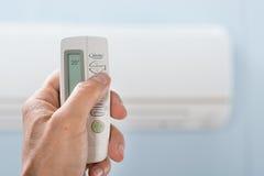 Mão da pessoa que mantém o condicionador de ar remoto Imagem de Stock Royalty Free