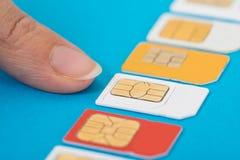Mão da pessoa que seleciona o cartão do sim Fotografia de Stock