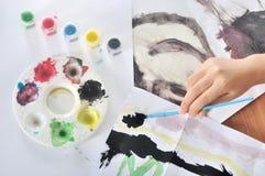 Mão da pintura da criança com escova e cor Foto de Stock Royalty Free