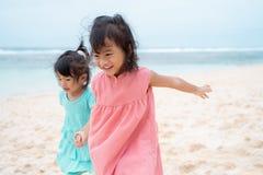 Mão da posse de duas meninas ao andar no litoral branco da areia imagem de stock royalty free