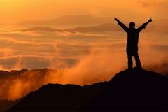 Mão da propagação do homem do turista da silhueta sobre a montanha Fotografia de Stock