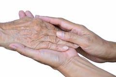 Mão da senhora idosa e da senhora mais nova que mantêm unida a parte traseira do branco do OM Foto de Stock Royalty Free