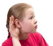 Mão da terra arrendada da menina na orelha. Fotos de Stock