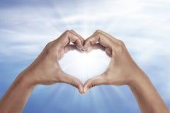 Mão dada forma coração com fundo do céu azul Imagem de Stock