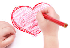 A mão das crianças com lápis desenha o coração Fotografia de Stock