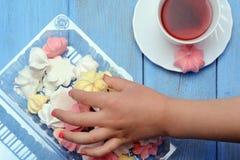 A mão das crianças está tomando fora da merengue da caixa Foto de Stock