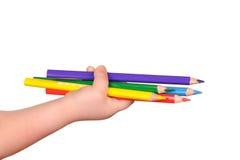 A mão das crianças prende os lápis coloridos Fotografia de Stock Royalty Free