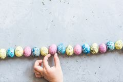 A mão das crianças que guarda os ovos da páscoa coloridos que que encontram-se no fundo concreto cinzento Configuração lisa Vista fotos de stock