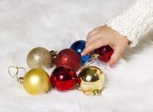 A mão das crianças que toma decorações da árvore de Natal Fotos de Stock Royalty Free