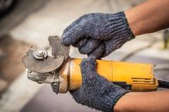 Mão das lâminas do moedor da posse do homem do trabalhador quebradas Perigos da utilização imagem de stock
