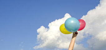 Mão das meninas que prende três balões coloridos fotos de stock royalty free