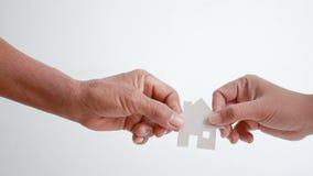 Mão das mulheres adultas que dão a casa do cartão de papel à metáfora e ao conceito da jovem mulher para a herança do ativo da mã vídeos de arquivo