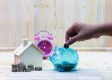 a mão das mulheres deixa cair moedas em um leitão claro na tabela de madeira fotografia de stock