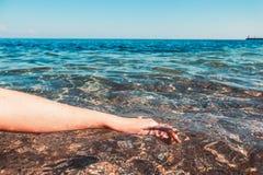 A m?o das mulheres no mar Close-up fotografia de stock