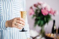 a mão das mulheres que guarda um vidro do champanhe no fundo da tabela festiva foto de stock royalty free