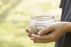 Mão das mulheres que guardam a garrafa do dinheiro da economia Fotografia de Stock Royalty Free