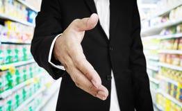 Mão de alargamento do homem de negócios com fundo do corredor do supermercado, foco seletivo fotos de stock royalty free
