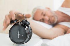Mão de alargamento do homem maduro ao despertador na cama fotos de stock royalty free