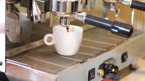 A mão de Barista pressiona a tecla 'Iniciar Cópias', os fluxos do café no copo branco video estoque