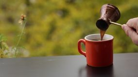 A mão de Barista que derrama o café quente saboroso no copo vermelho fabricou cerveja no potenciômetro turco tradicional, tabela  video estoque