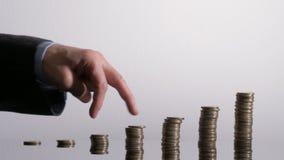 A mão de Businessmantoma uma caminhada sobre as pilhas da moeda video estoque