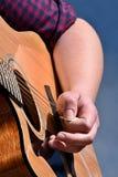 Mão de cordas impressionantes do guitarrista fêmea na guitarra acústica com picareta Fotografia de Stock Royalty Free