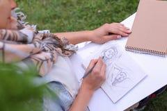 Mão de cursos do lápis de Makes Sure Sharp do artista da menina no álbum Pag Imagens de Stock Royalty Free