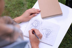 Mão de cursos do lápis de Makes Sure Sharp do artista da menina no álbum Pag Fotografia de Stock Royalty Free