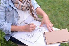 Mão de cursos do lápis de Makes Sure Sharp do artista da menina no álbum Pag Imagem de Stock Royalty Free