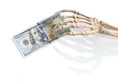 Mão de esqueleto com dinheiro Fotografia de Stock Royalty Free