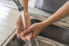 Mão de lavagem da mulher na cozinha fotografia de stock royalty free