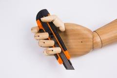 Mão de madeira com a faca de corte do escritório Fotografia de Stock
