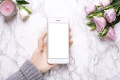 Mão de madeira com telefone celular no fundo de mármore do escritório com flores cor-de-rosa fotos de stock royalty free