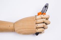 Mão de madeira que guarda alicates Imagens de Stock