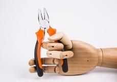 Mão de madeira que guarda alicates Fotografia de Stock