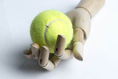 Mão de madeira que guarda uma bola de tênis foto de stock