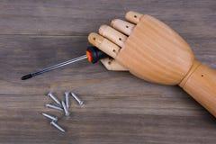 Mão de madeira que guarda uma chave de fenda Phillips Foto de Stock Royalty Free