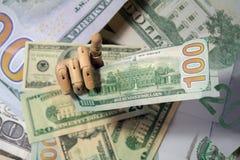 Mão de madeira que mantém o detalhe ascendente próximo dos dólares macro Imagens de Stock