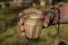 Mão de Men's que guarda o cappuccino delicioso em um vidro Imagem de Stock Royalty Free