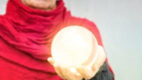 A mão de mulher mais idosa que guarda uma esfera de vidro brilhante foto de stock royalty free
