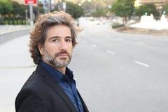 MÃO-DE-OBRA Vestindo no terno escuro um considerável, 'sexy', o homem de negócios da Idade Média é parte externa ereta nas ruas d foto de stock royalty free