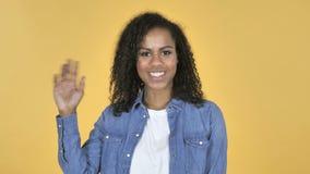 Mão de ondulação da menina africana a dar boas-vindas isolado no fundo amarelo filme